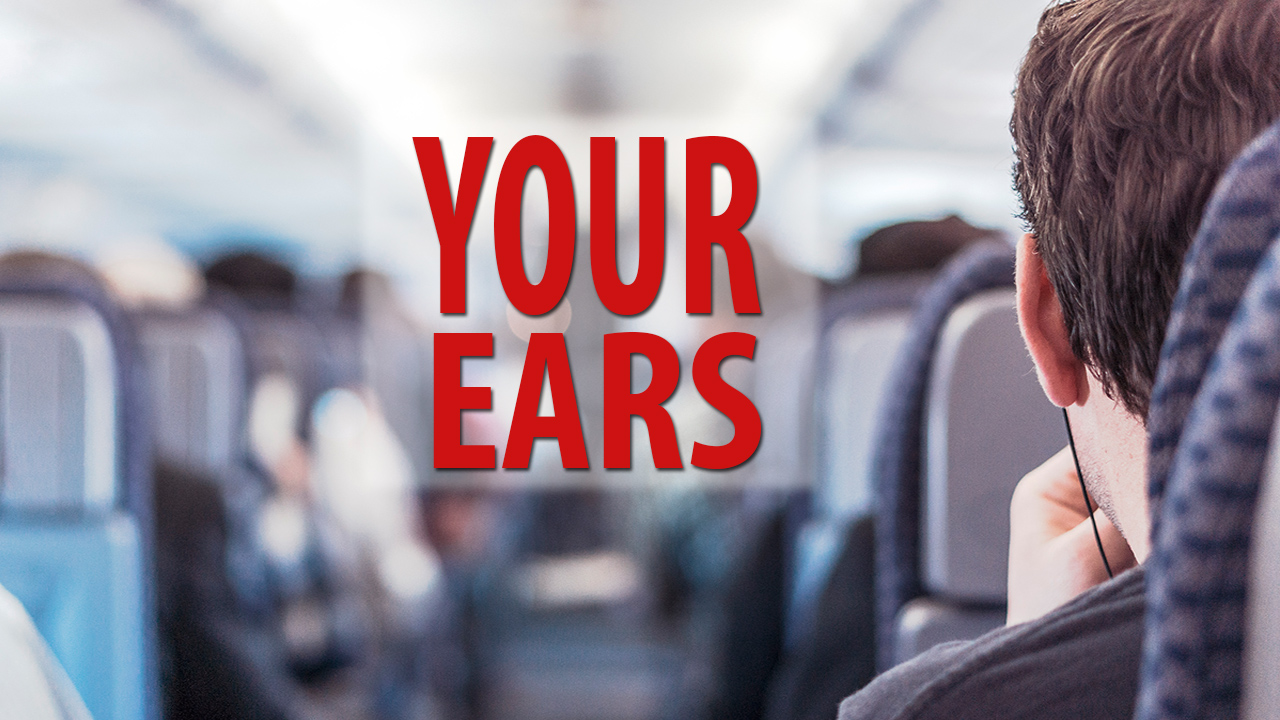 blog post image of a man sitting on a plane with headphones on